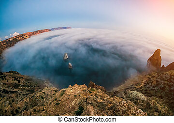 Selective focus. Misty Sea coast at sunset. Clouds and fog over the rocky seashore. Silhouette of cliff. Copy space. The concept of an travel, relax, active and healthy life in harmony with nature.