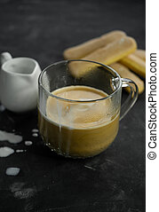 selective focus, mug of hot coffee with cream and cookies