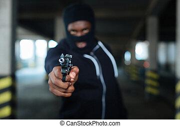 Selective focus of a handgun muzzle aimed at you
