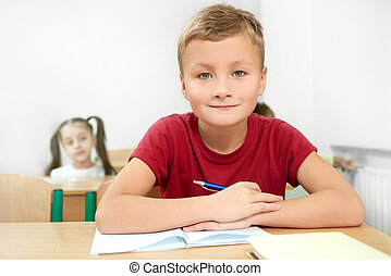 Selective focus of cheerful boy sitting at desk in classroom