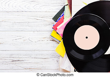 selective focus of selective focus image of records stack with record on top over wooden table. vintage filtered