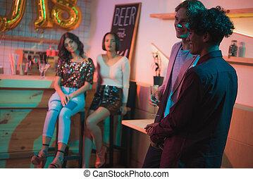 multiethnic men having conversation in bar - selective focus...