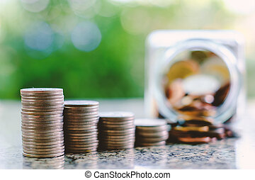 Selective focus of stack of coins on blurred the glass jar