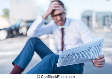 stressed businessman with newspaper