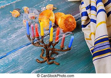 Selective focus of the Hanukkah Jewish holiday with traditional menorah, donuts
