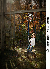 Selective Focus of woman on swing, autumn