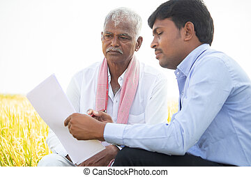 Selective focus on farmer, Bank officer explaning about farm loan paper documents to Indian farmer near agriculture field - concpet of Indian villger banking and lifestyle
