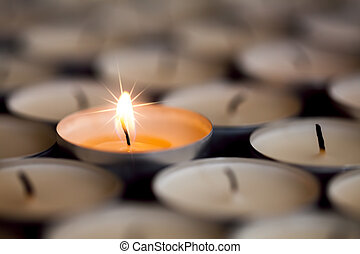 Selective focus on light from a single sparkling flame from one candle among many extinguished tealight candles.