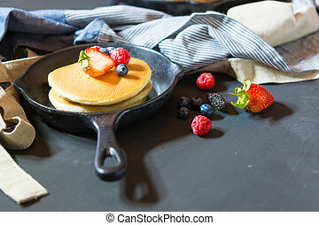 Pancakes with blueberries & raspberry on wood background
