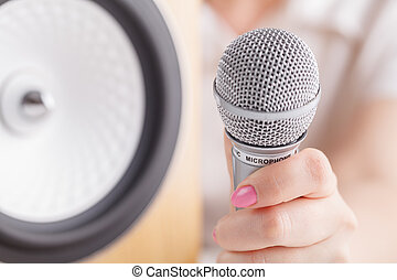 Selective focus photo of microphone in human hand