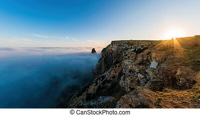 Selective focus. Scenery with shining sun in the sky over the misty Sea coast at sunset. Clouds and fog over the rocky seashore. Copy space. The concept of calmness, silence and unity with nature.