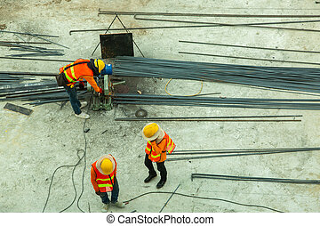 Selective focus to construction worker and many steel bar working with electric iron cutting machine at the construction site.