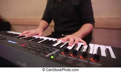 Selective focus to man keyboard player fingers. There are musical instrument for concert or learning music. Close up hand of man musician playing the piano on rehaersal at studio.