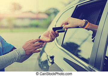 Selective focus to woman pay credit card with staff for fuel.