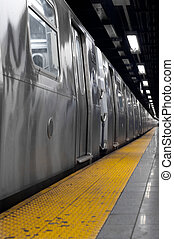 Selective monochrome of a NYC Subway train waiting in a station