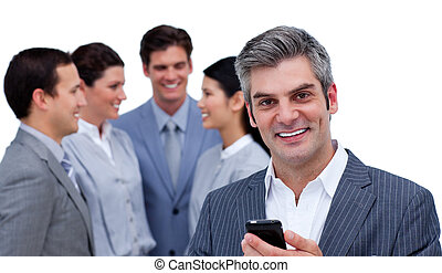 Self-assured businessman on phone standing in front of his team