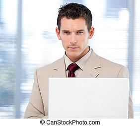 Self-assured businessman using a laptop standing