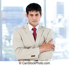 Self-assured businessman with folded arms standing