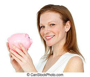 Self-assured businesswoman holding a piggybank