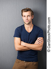 Self-assured handsome man standing with his arms crossed in...