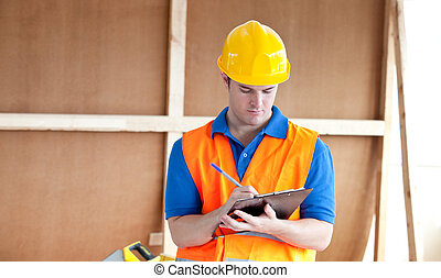Self-assured male worker writing on a clipboard at work