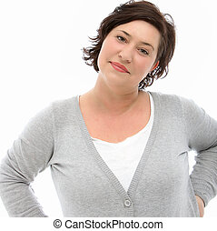 Self-assured middle-aged woman at peace with herself standing with her hands on her hips looking at the camera