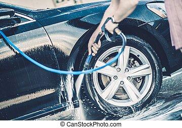 Self Car Washing. Cleaning Wheels Using High Pressure Water.