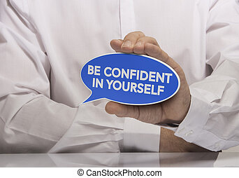 Image of a man hand holding blue speech balloon with the text be confident in yourself, white shirt and reflexion. Concept and motivation for self confidence