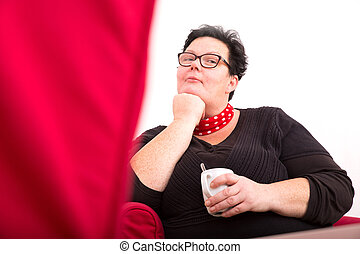 Self confident - A relaxed woman sitting in the living room.