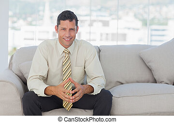 Self-confident businessman sitting on sofa in bright office