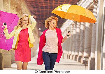 Self-confident girls walking with umbrellas - Self-confident...