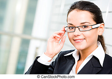 Self-confident woman in suit touching her glasses