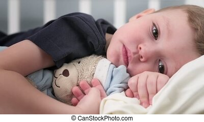 Self-contained little boy who is in state of depression and alone without the support of his mother and father lies in bed hugging teddy bear. Concept of self-isolation and psychological disorder kid.
