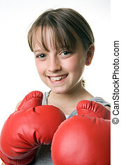 A smiling young girl with boxing gloves on