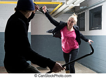 Self defence - Young woman defending herself with her purse...
