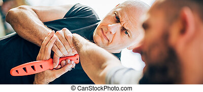 Self defense disarming technique against threat and knife...
