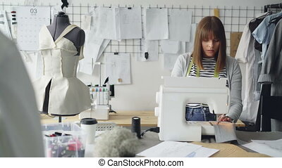 Self-employed clothing designer is working with sewing...