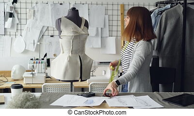 Self-employed female tailor is checking clothing patterns...