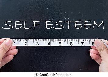 Tape measure aligned against the word self esteem handwritten on a chalkboard