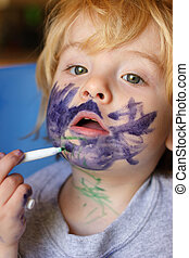 a young toddler exploring art by drawing on his face with a marker