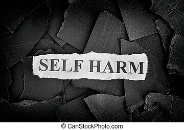 Self Harm. Torn pieces of black paper and words Self Harm....