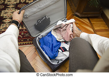 Self point of view of man packing suitcase with clothes