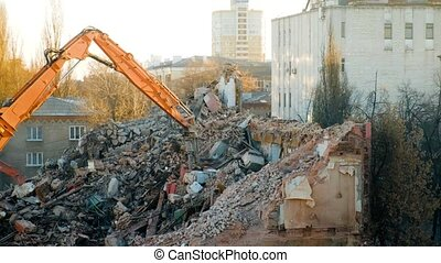 Self-propelled crane Bucket wedge-hammer excavator rakes the destroyed remains of the building. Demolition of the building. Russia, Voronezh.