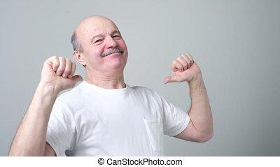 Self satisfied and proud senior man haughtily looks forward...