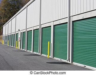 Self Storage Units - Row of outdoor green door self-storage...