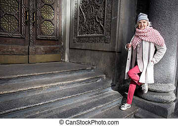 Self-sufficient mature lady standing near architectural gate...