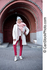 Self-sufficient senior lady standing near historic building ...