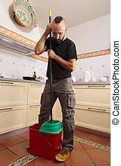 Self-sufficient young hispanic man squeezing the mop - Self-...