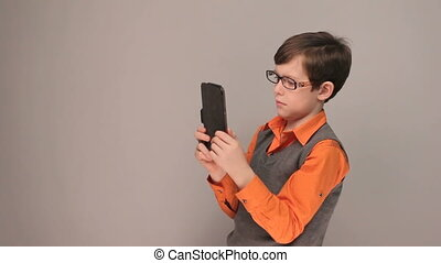 Self Teen boy shoots himself at the plate in glasses on gray background