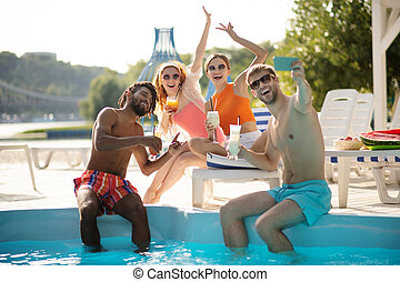 Happy couples making selfie all together having pool party